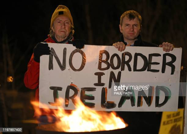 Activists hold up a placard during a protest organised by Border Communities Against Brexit on January 31 on the border at Carrickarnon, Northern...
