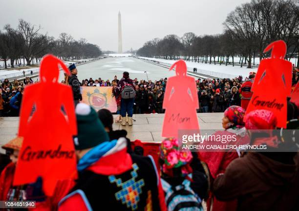 Activists hold up a sign as they listen to speakers during the Indigenous People's March on the National Mall at the Lincoln Memorial in Washington...