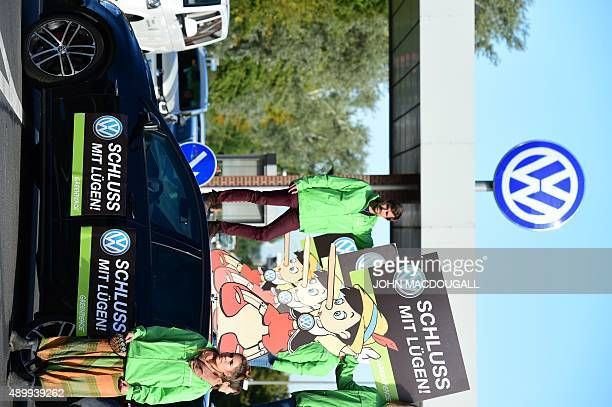 Activists hold up a sign reading 'Stop Lying' while standing on a VW car during a protest of environmental watchdog Greenpeace in front of the...