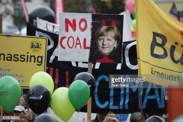 Activists hold up banners including one that shows German Chancellor Angela Merkel with devil horns at a protest march to demonstrate against coal...