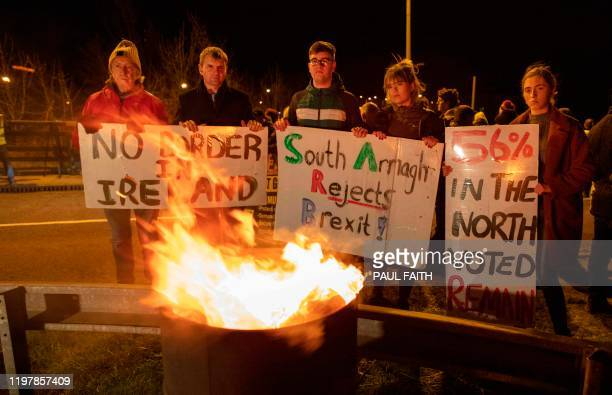 Activists hold up placards as they try to keep warm during a protest organised by Border Communities Against Brexit on January 31 on the border at...