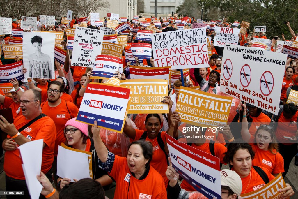 Activists hold up signs at the Florida State Capitol as they rally for gun reform legislation on February 26, 2018 in Tallahassee, Florida. In the wake of the February 14 school shooting that left 17 people dead, hundreds of people joined the Parkland students to call for gun reform.