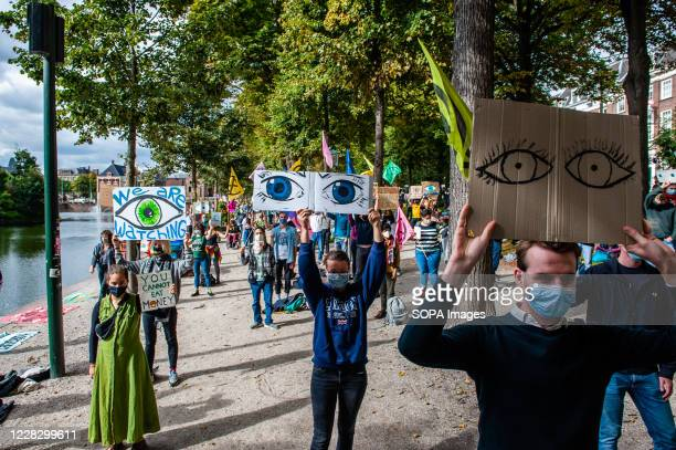 Activists holding placards with eyes drawn on them during the demonstration. The climate activist group, Extinction Rebellion in The Netherlands has...