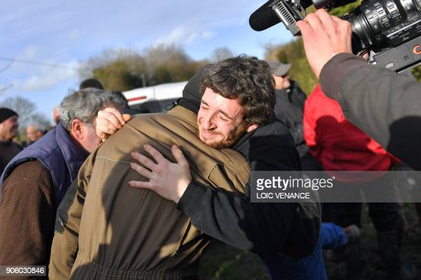 Activists hug each other as they celebrate at La Vache rit a farm in the 'Zad' of NotreDamedesLandes after French prime minister announced the French...