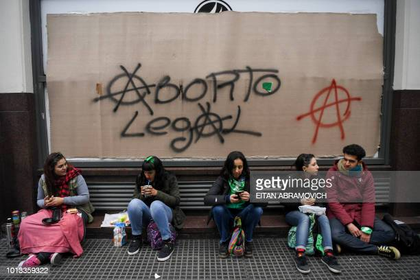Activists in favour of the legalization of abortion wait in front of a graffiti reading 'Legal Abortion' in the surroundings of the National Congress...