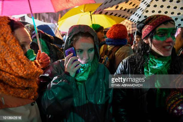 Activists in favour of the legalization of abortion wait outside the National Congress in Buenos Aires on August 9 2018 while senators debate the...