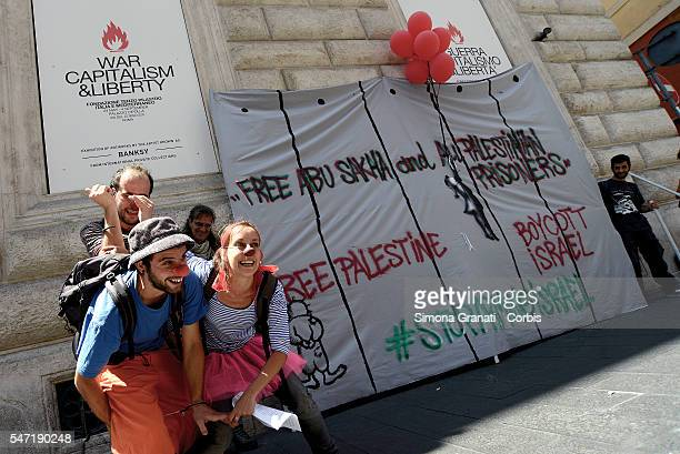 Activists in solidarity with the Palestinian people at the exibition of Banksy at Palazzo Cipolla reproducing the famous little girl with red...