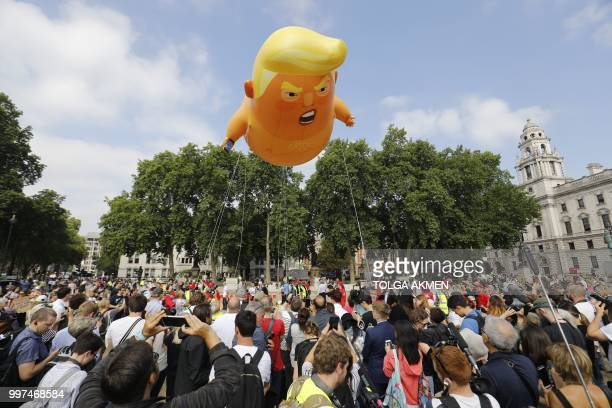 TOPSHOT Activists inflate a giant balloon depicting US President Donald Trump as an orange baby during a demonstration against Trump's visit to the...