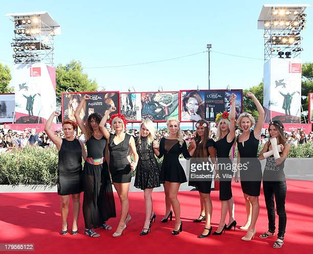FEMEN activists Inna Shevchenko and Sasha Shevchenko pose with other members of the group on the red carpet before the Sacro GRA Premiere during the...