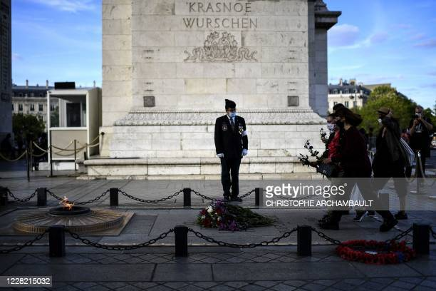 Activists lay flowers on the tomb of the Unknown Soldier during a gathering to mark the 50th anniversary of the first demonstration of French...