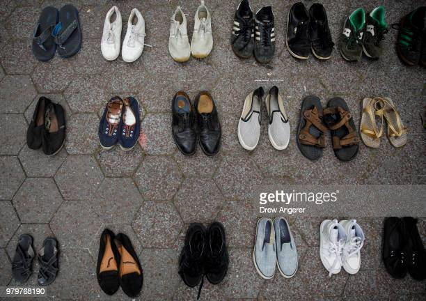 Activists leave their shoes on the ground to represent refugees during a rally to support immigrants and to mark World Refugee Day June 20 2018 in...