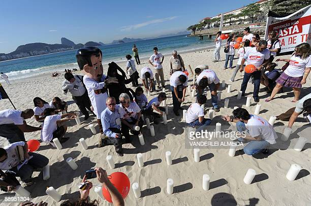 Activists light 100 candles during a demonstration July 9 2009 at Copacabana Beach Rio de Janeiro Brazil commemorating the 100th anniversary of the...