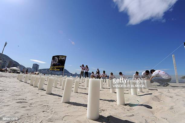 Activists light 100 candles during a demonstration July 9, 2009 at Copacabana Beach, Rio de Janeiro, Brazil, commemorating the 100th anniversary of...
