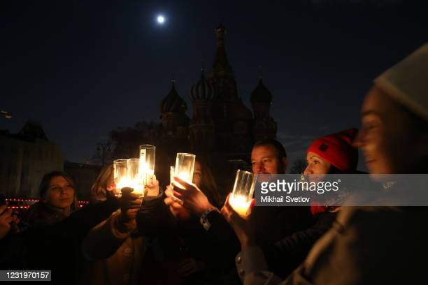 Activists light candles for Earth Hour in front of a darkened St.Basile's Cathedral at the Red Square, on March 2021, in Moscow, Russia. The Moscow...