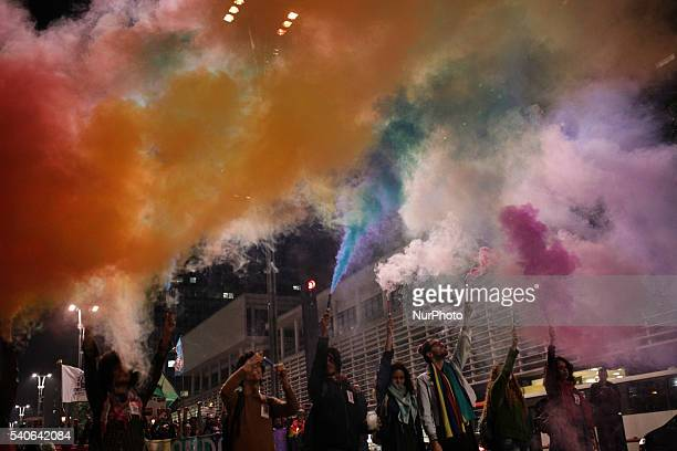 Activists light up flares of the LGBT colors during a vigil in memory of victims of the mass shooting at the Pulse gay night club in Orlando in Sao...