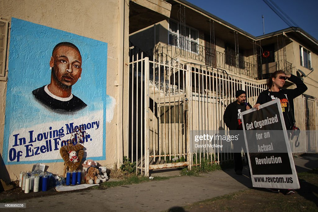 Activists look at a mural of Ezell Ford, a 25-year-old mentally ill black man, at the site where he was shot and killed by two LAPD officers in August, on December 29, 2014 in Los Angeles, California. The long-awaited autopsy report, which was put on a security hold at the request of police and ordered by L.A. Mayor Eric Garcetti to be made public before the end of 2014, was released December 29.