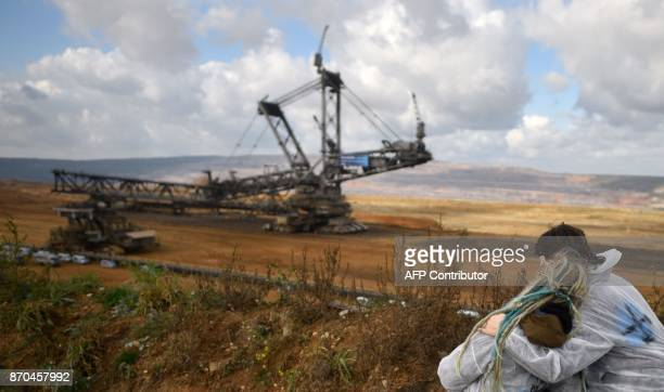 Activists look on as policemen prevent other environmentalists to march further after they managed to enter the Hambach lignite open pit mine near...