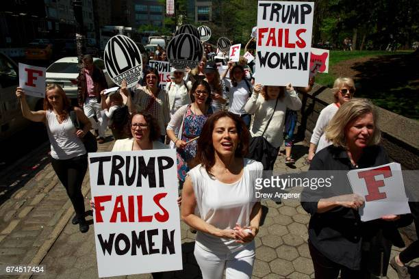 Activists march along 59th Street during a protest against President Donald Trump's policies concerning women's issues, April 28, 2017 in New York...
