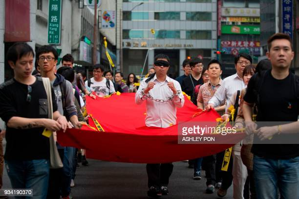 TOPSHOT Activists march during the Commemorating Lee MingChes One Year Of Imprisonment Protest in Taipei on March 19 2018 Taiwanese human rights...
