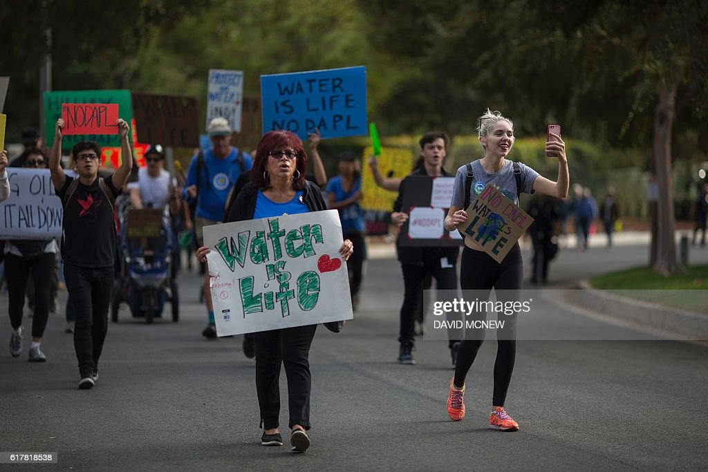 Activists march to a site near a Hillary Clinton presidential campaign fundraiser with US President Barack Obama to call for a halt to the Dakota Access Pipeline project, October 24, 2016 in Beverly Hills, California. / AFP / DAVID