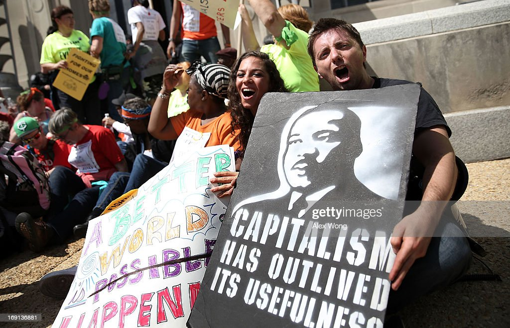 Activists occupy one of the entrances as they participate in civil disobedience during a protest outside the U.S. Justice Department May 20, 2013 in Washington, DC. Homeowners and activists from Home Defenders League and Occupy Homes joined the protest to demand that Attorney General Eric Holder 'hold Wall Street Banks that ravaged America's economy accountable.'