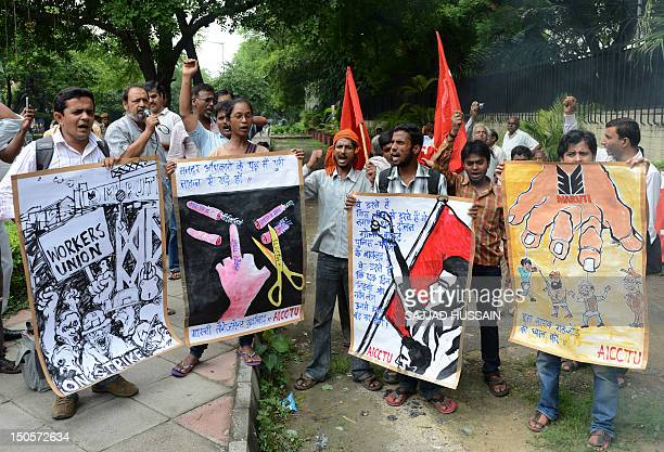 Activists of all India Central Council of Trade Union shout slogans in front a burning effigy of the Maruti management during a protest in New Delhi...