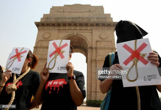Activists of Amnesty International India wear black hoods and a noose around their necks as they protest against the death penalty in New Delhi on...