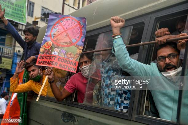 TOPSHOT Activists of Bharatiya Janata Party shout slogans holding posters as they sit in a police van during an antiChina protest in Siliguri on June...