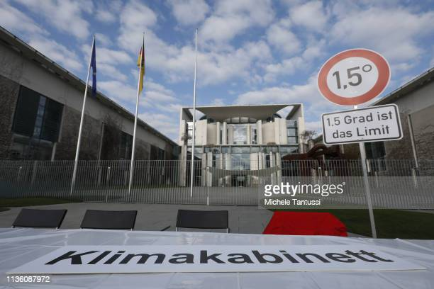 Activists of Campact protest against climate change with a traffic sign readings 15 grad is the limit as the weekly government cabinet and the...