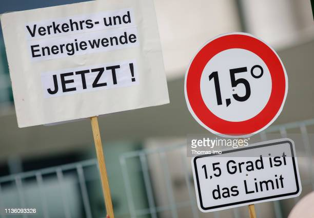 Activists of Campact protest against climate change with a traffic sign readings 15 grad is the limit as the weekly government cabinet meets on April...