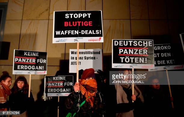 Activists of Campact Urgewald and Adopt a Revolution display placards calling on Germany to hold weapon exports to Turkey in front of the Bavarian...
