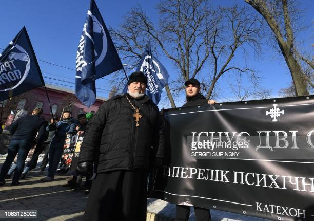 Activists of far-right groups hold placards and flags as they protest against the transgender rights march in Kiev on November 18, 2018. - Two...