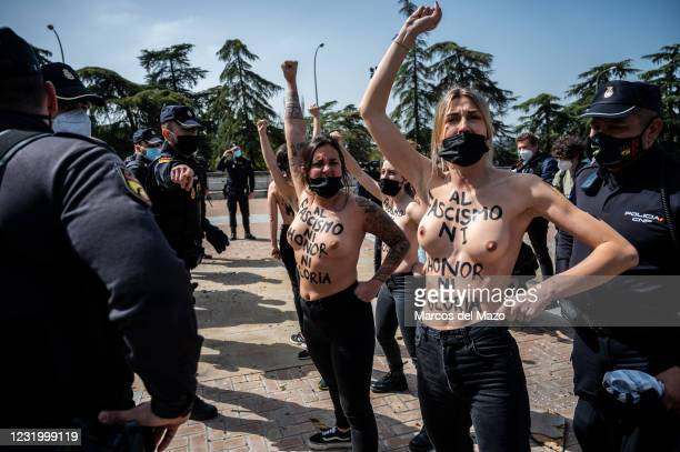 Activists of feminist group FEMEN with their body painted with messages against fascism, raising their fist in front of police during a gathering of...