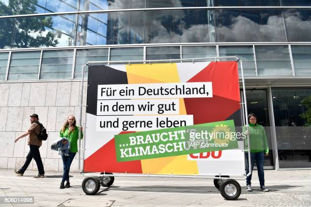 Activists of Germany's Greens pose in front of the headquarters of the conservative Christian Democratic Union party with an altered CDU campaign...
