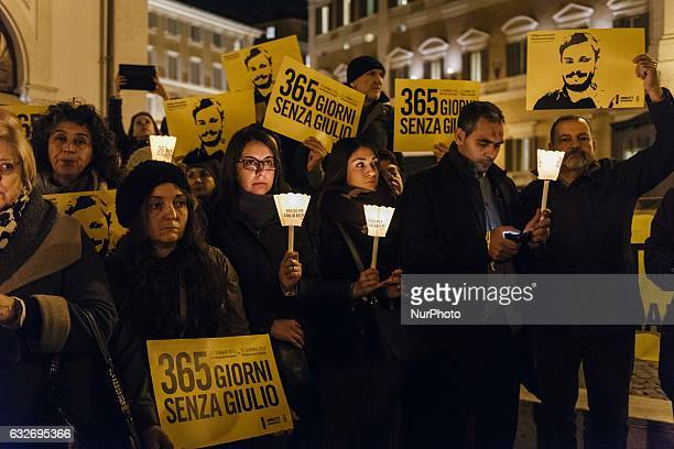 Activists of human rights organization Amnesty International hold candles as they take part in a demonstration in front of the Palazzo Montecitorio...