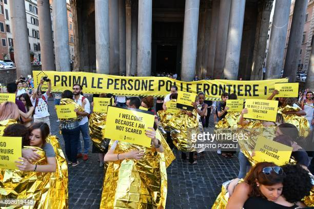 Activists of human rights organization Amnesty International hug in front of a banner reading 'People first then borders' near the Pantheon during a...