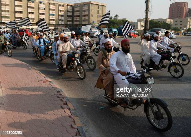 Activists of Jamiat Ulemae Islam carry party flags as they march in a rally in Karachi on October 25 2019 JUI chief Maulana FazalurRehman had...