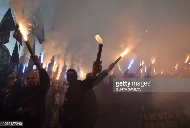 TOPSHOT Activists of nationalists movements light flares and shout slogans during a rally in Kiev on October 14 2018 on the Intercession of the...