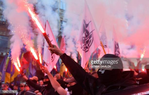 TOPSHOT Activists of nationalists movements light flares and shout slogans during a rally in Kiev on October 14 on the Intercession of the Virgin...
