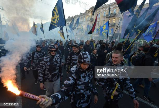 TOPSHOT Activists of nationalists movements light flares during a rally in Kiev on October 14 on the Intercession of the Virgin Mary which is...
