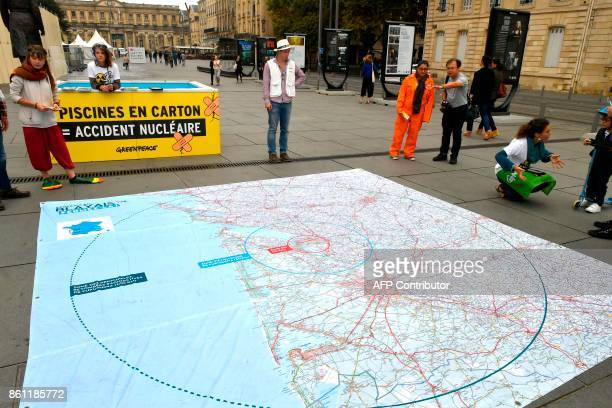 Activists of non-governmental organization Greenpeace distribute leaflets and display a large map of France with the place of the power plant near...
