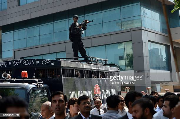 Activists of Pakistan TehreekeInsaf gather around a police prison van carrying arrested workers to prevent them from leaving the court area in...
