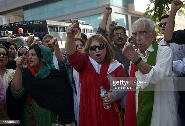 Activists of Pakistan TehreekeInsaf shout slogans as they gather around a police prison van carrying arrested workers to prevent them from leaving...