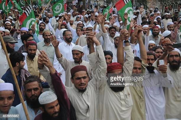 Activists of Pakistani religious party Ahle Sunnat Wal Jamaat shout slogans as they march during an anti Imran Khan and TahirulQadri protest rally on...