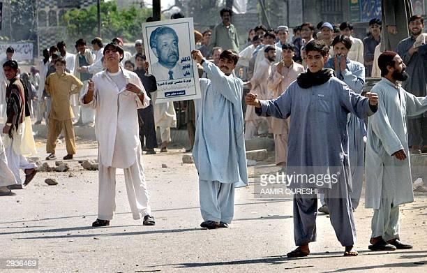 Activists of Pakistan's fundamentalist sixparty religious alliance Muttahida MajliseAmal display a portrait of disgraced nuclear scientist Dr Abdul...