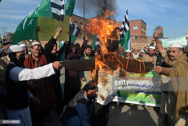 Activists of Rah e Haq Party burn an effigy to represent Iran and the United States during a protest in Peshawar on January 5 in the support of Saudi...