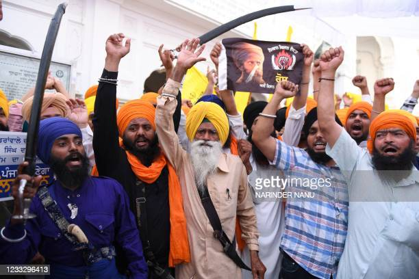 Activists of Sikh organisations hold swords as they shout pro-Khalistan and anti-government slogans after offering prayers on the occasion of the...