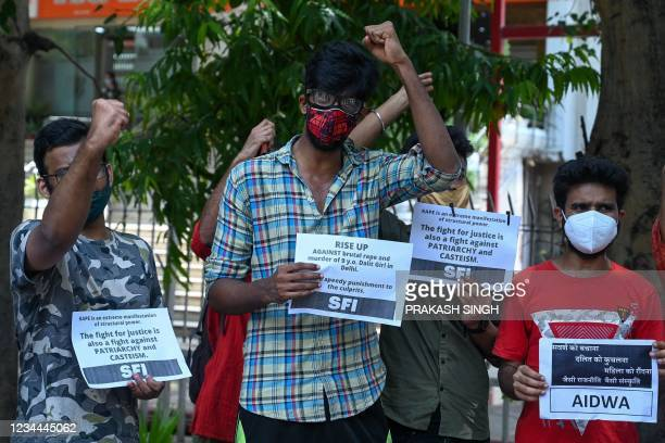 Activists of Student Federation of India and All India Democratic Women's Association hold placards during a protest against the alleged rape and...