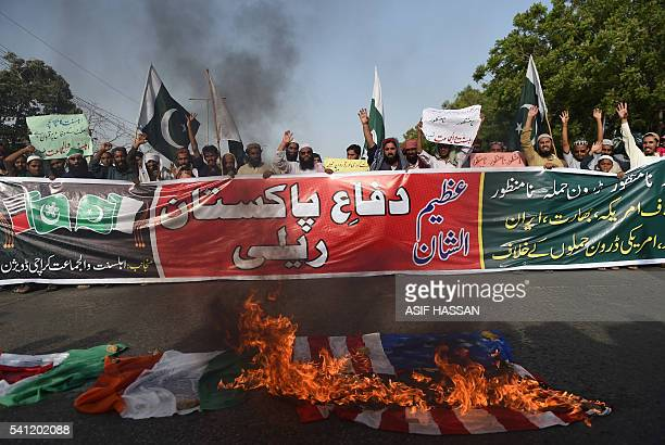 Activists of the Ahle Sunnat Wal Jamaat group burn US and Indian flags during a protest against US missile strikes in Pakistan in Karachi on June 19...