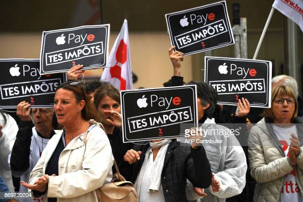 Activists of the Association for the Taxation of financial Transactions and Citizen's Action hold a sign reading Apple pay your taxes outside the...